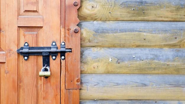 Oude houten deur met een zwarte metalen bout. close-up van een slot en grendel op een houten deur. rustieke houten metalen deurklink. dit schuifslot kan worden gebruikt op luifels, op bureaubladen of op hekken.