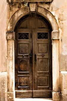 Oude houten deur met slot in oude stenen muur. getinte foto.