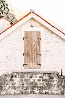 Oude houten deur naar de zolder in een witte muur met een oranje dak