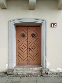 Oude houten deur op huizenvoorgevel met nummer