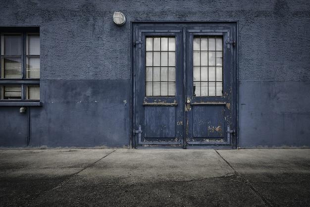 Oude houten deur van een blauw gebouw overdag