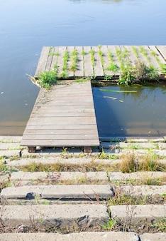 Oude houten dok met meer dan troebel water