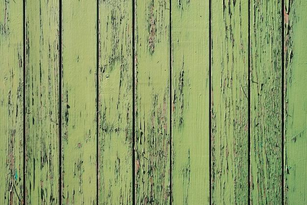 Oude houten geschilderde rustieke muur met groene vlokkige kleurstof.