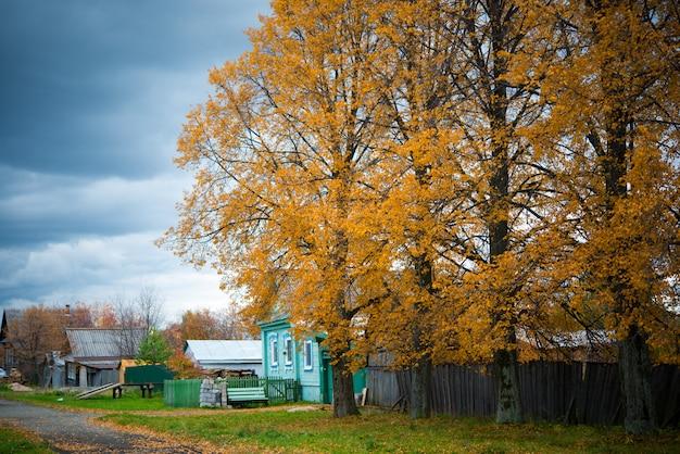 Oude houten huis in het dorp, bomen, landschap van het platteland in de herfst