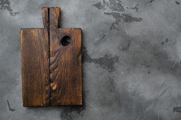 Oude houten keukenbordset, bovenaanzicht plat, met kopieerruimte voor tekst of eten, op grijze stenen tafelachtergrond
