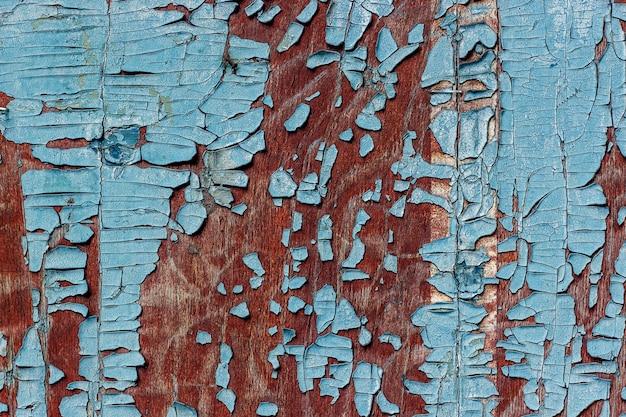 Oude houten oppervlak in een bruine kleur met stukjes peeling blauwe verf.