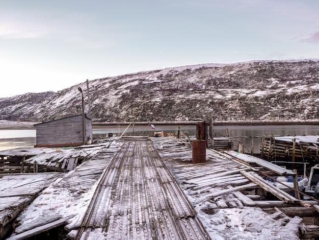 Oude houten pier in de baai van de barentsz-zee. teriberka. rusland.