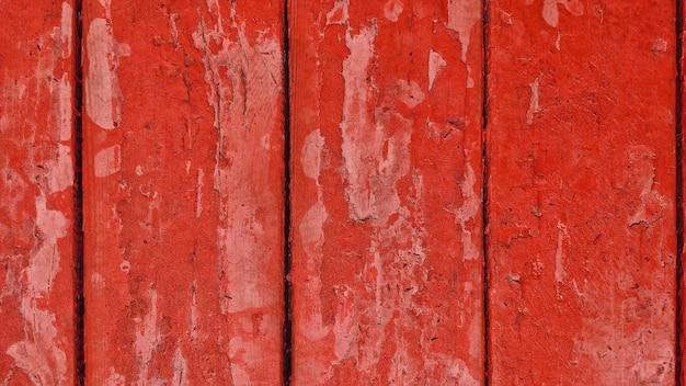 Oude houten planken met rode afbladderende verf met scheuren.