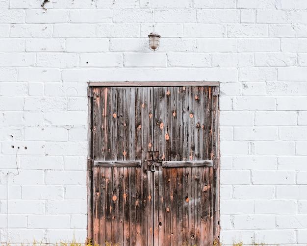 Oude houten poort in een witte bakstenen muur