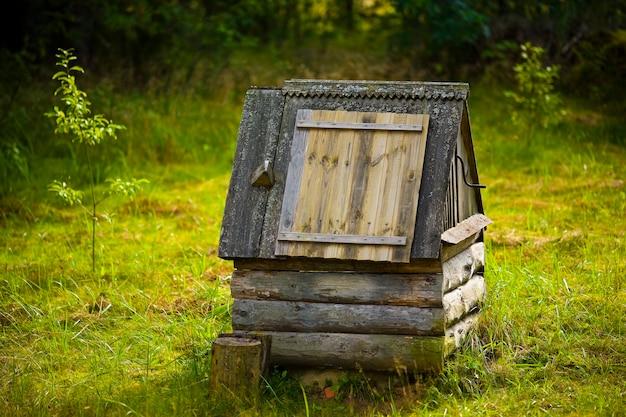 Oude houten put in het dorp bij zonsondergang.