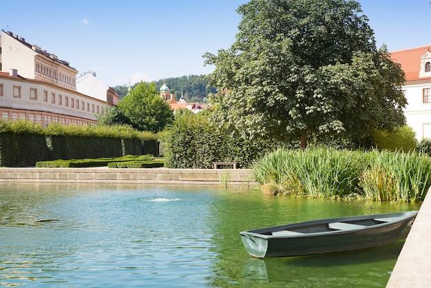 Oude houten roeiboot afgemeerd in tuin met zonstijging