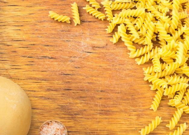 Oude houten snijplank en droge pasta met deeg. gastronomie achtergrond