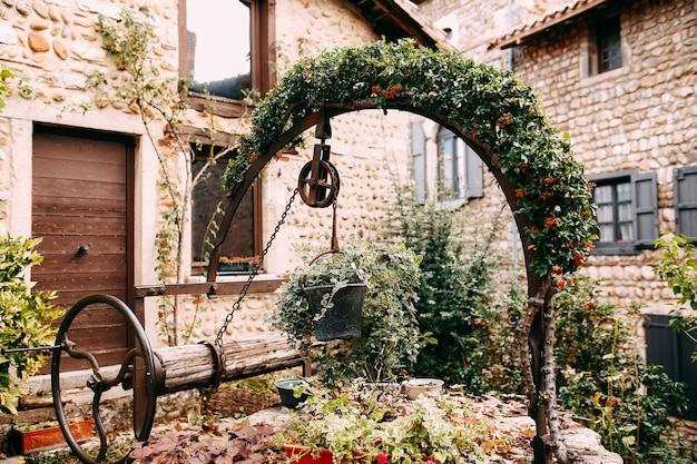 Oude houten steen goed met rode bloem boog en klimop in perouges, frankrijk.