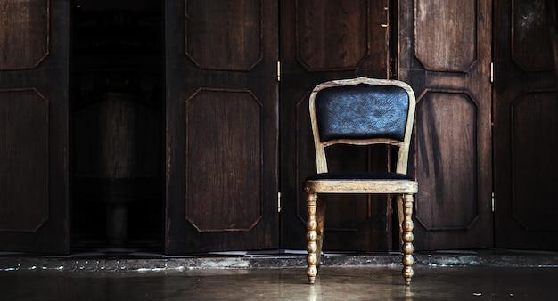 Oude houten stoel leeg op donkere kamer