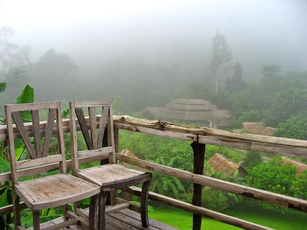 Oude houten stoelen op houten veranda met groene boom en mist in de ochtend.