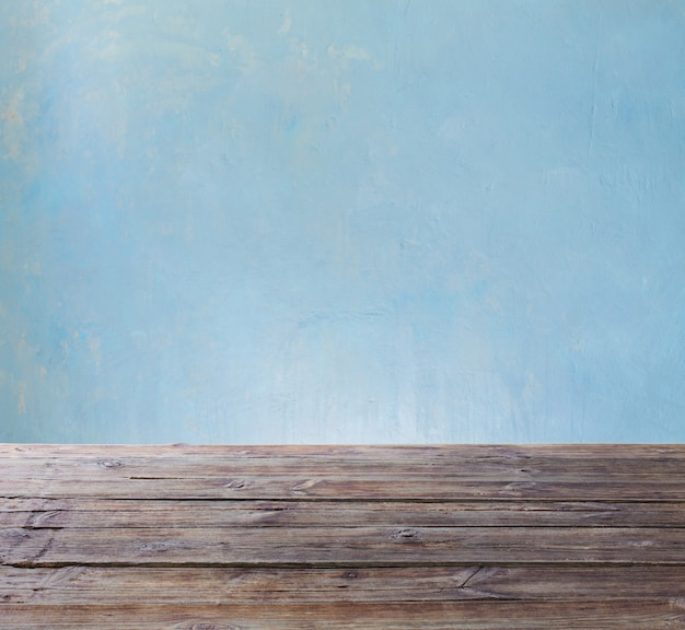 Oude houten tafel op blauwe muur als achtergrond