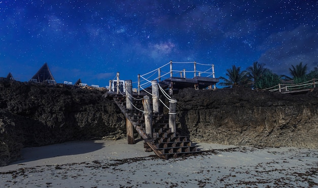 Oude houten trap die leidt naar het hotel op de achtergrond van de sterrenhemel nacht landschap afrika, tanzania, zanzibar