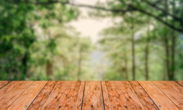 Oude houten vloer naast een wazig bos met felle zonneschijn in het midden