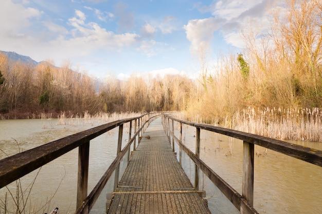 Oude houten voetgangersbrug op lagune. buiten en natuur. landelijk panorama Premium Foto