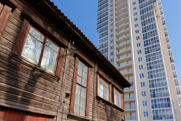 Oude houten woongebouw op de achtergrond van een nieuw hoog gebouw