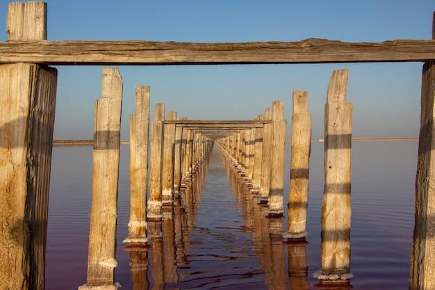 Oude houten zuilen staan achter elkaar in een roze meer, ze worden gebruikt om roze zout uit het meer te halen