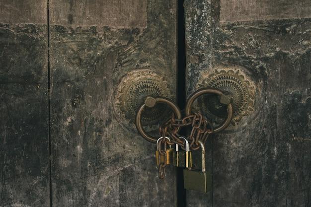 Oude huisdeur die met moderne sleutelsachtergrond wordt gesloten