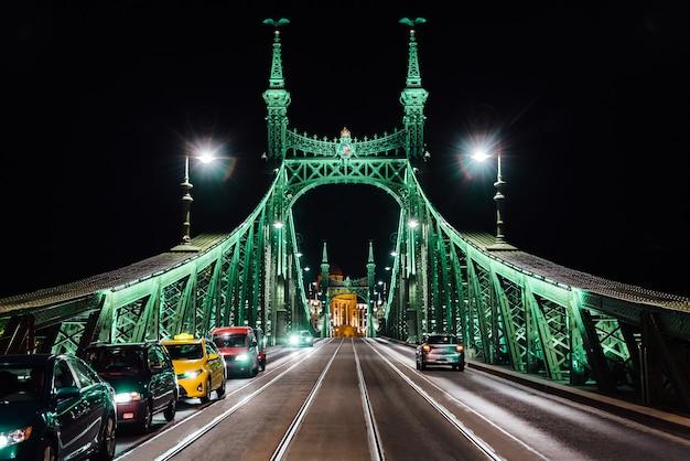 Oude ijzeren brug 's nachts in het licht van straatverlichting over de rivier de donau in boedapest, hongarije