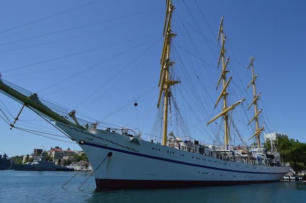 Oude jacht met verlaagde zeilen afgemeerd in de haven