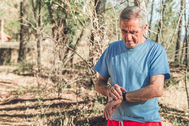 Oude jogger die zijn handwatch controleert na het rennen