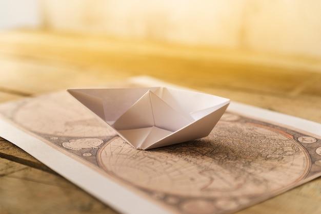 Oude kaart met papieren boot