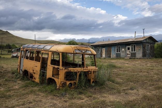 Oude kapotte bus op een veld door een huis gevangen in armenië