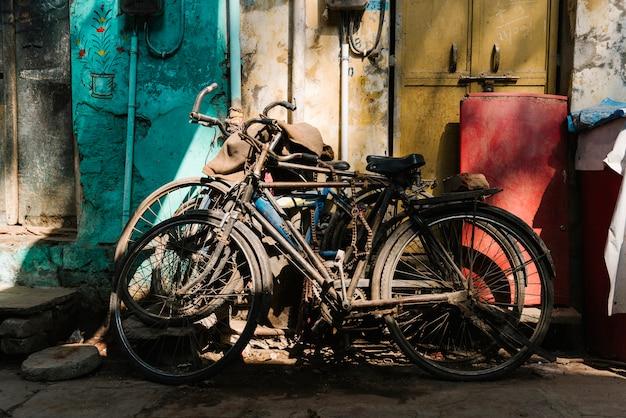Oude kapotte fietsen die buiten het huis zijn achtergelaten