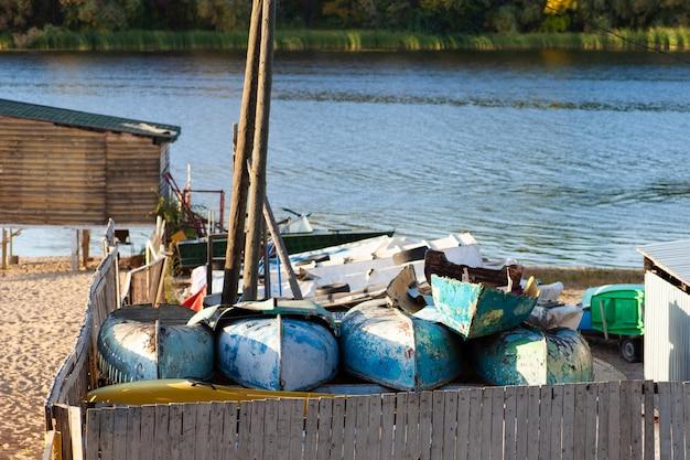 Oude kapotte vissersboten worden opgestapeld bij een bootstation bij de rivier.