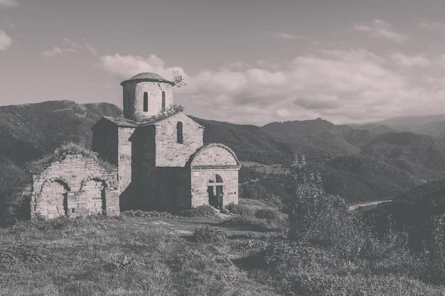 Oude kerk in bergen, in nationaal park dombai, kaukasus, rusland. zomerlandschap, zonnig weer, dramatische blauwe lucht en zonnige dag