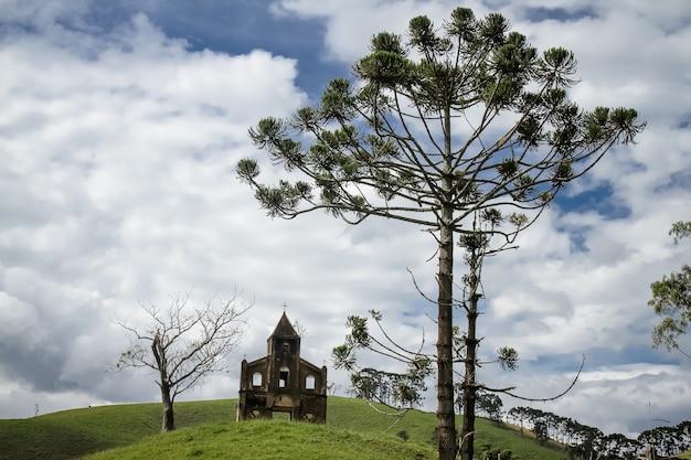 Oude kerk in de bergen met bomen vooraan en achtergrond met prachtig landschap