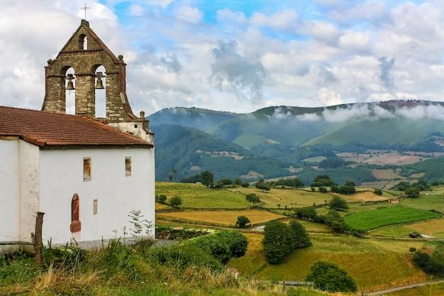 Oude kerk met klokkentoren in het groene veld met hoge bergen. asturië spanje europa.