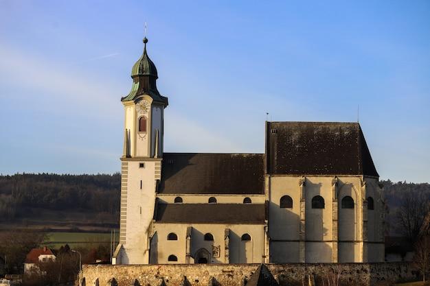 Oude kerk op de top van een heuvel achter de bergen van een kleine stad in oostenrijk, melk.