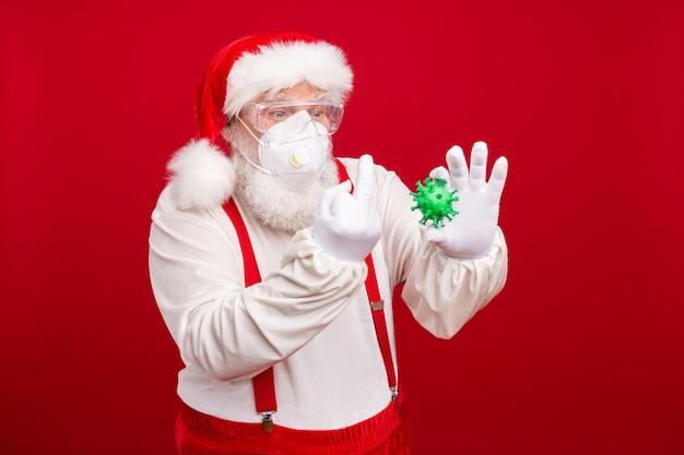 Oude kerstman draagt een beschermend medisch masker op afstand kerstviering