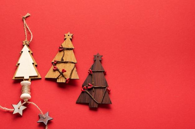 Oude kerstobjecten houten dennenboom en rood koord, sneeuwvlokken op rode achtergrond. kerst spandoek. bovenaanzicht. plat leggen. bespotten.