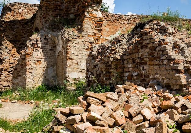 Oude klei oranje bakstenen in een verlaten verwoeste rode bakstenen gebouw, kasteelruïne in europa