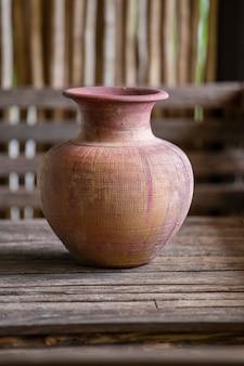 Oude klei vaas met handmatig werk op houten tafel in thais huis, close-up