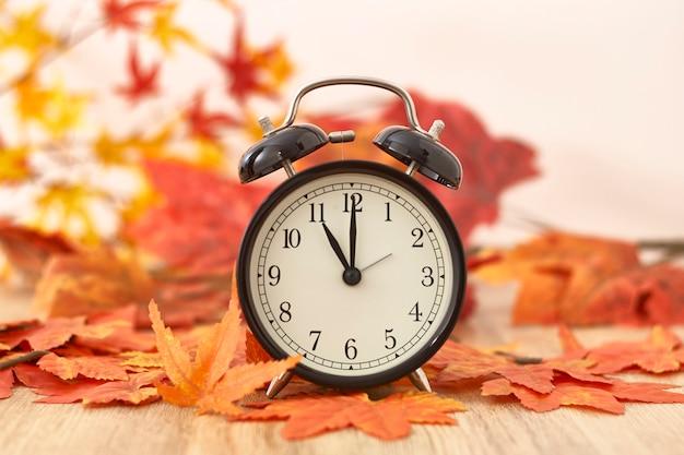 Oude klok op de herfstbladeren op houten lijst