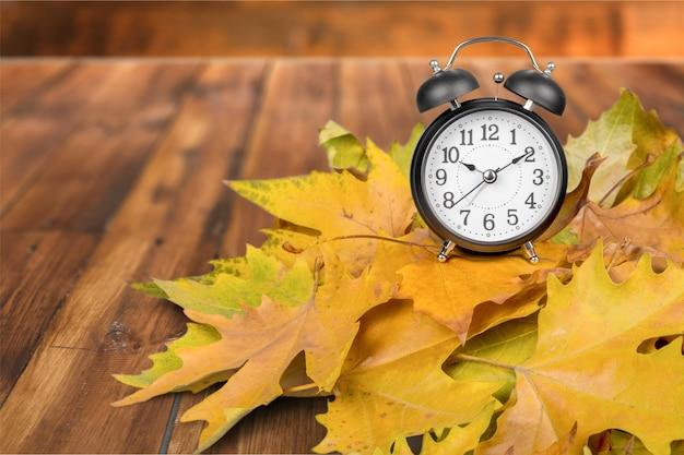 Oude klok op herfstbladeren op houten tafel