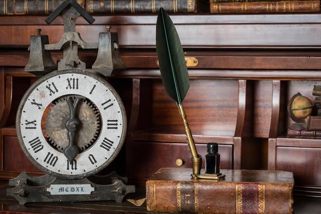 Oude klok op plank met oude boeken en pen