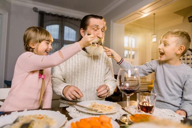 Oude knappe grootvader met zijn twee kleinkinderen zitten aan de keukentafel en eten pasta. klein meisje en jongen grootvader voeden met pasta en lachen