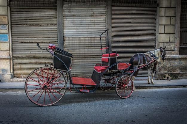 Oude koets op straat met paard