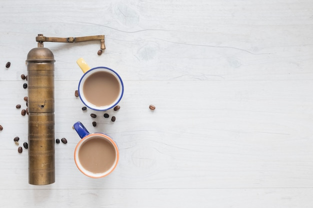 Oude koffiemolen en koffiebonen met hete koffie op houten achtergrond