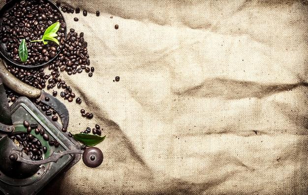 Oude koffiestijl. geroosterde graankoffie met kaneel en verschillende oude gereedschappen. op een stoffen zak.