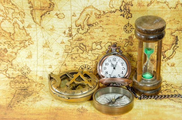 Oude kompas en zandloper op een oude wereldkaart