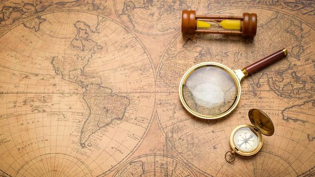Oude kompas, vergrootglas en zand klok op vintage kaart